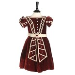 An unusual commemorative child's dress, 1863, of burgundy velvet with ivory satin piping,
