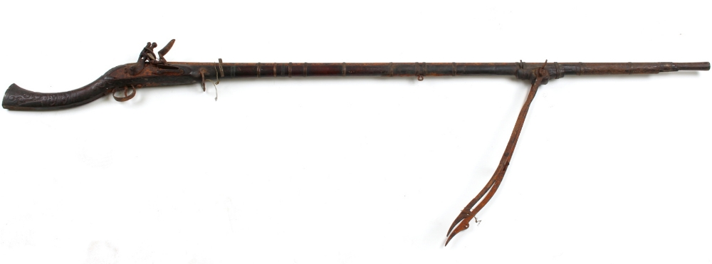 An early 19th century Middle Eastern flintlock jezail, with carved decoration to stock, 66ins. (