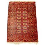 Property of a lady - an early / mid 20th century Turkoman rug, with two columns of guls, 63 by