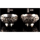 A pair of late 19th / early 20th century Japanese silver bowls, with repousse dragon decorations &