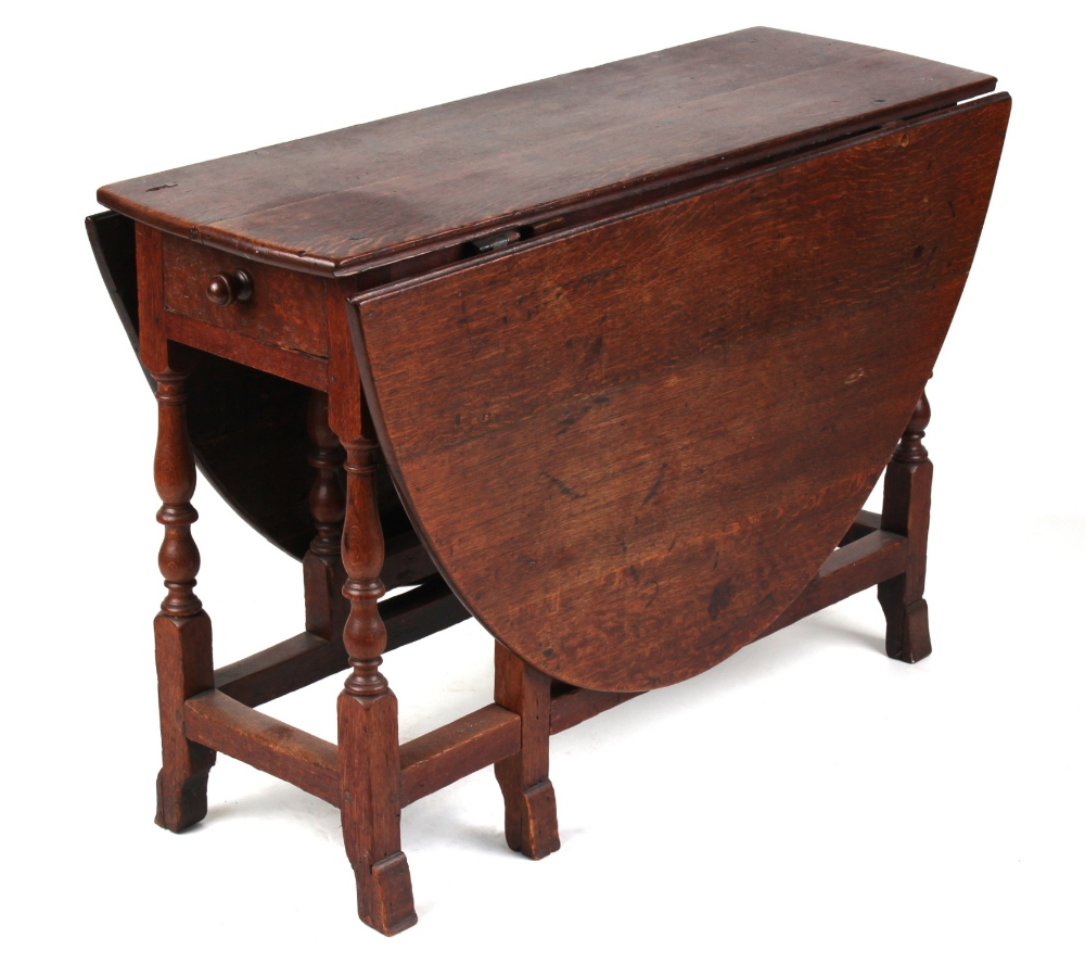 Lot 123 - Property of a gentleman - an 18th century oak oval topped gate-leg dining table, with end drawer, on