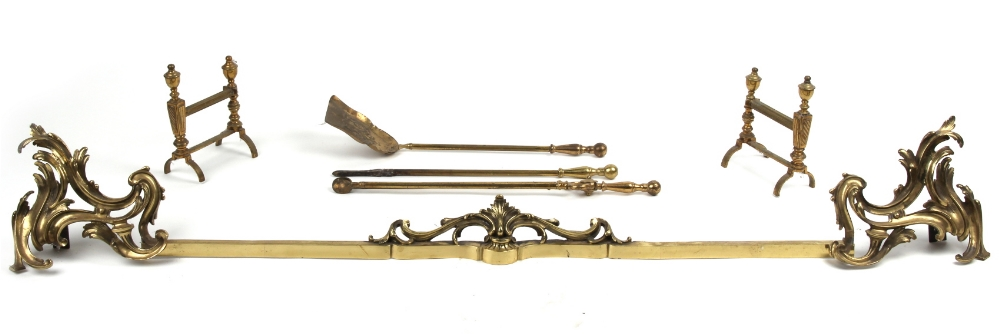Property of a lady - a French Louis XV style gilt brass rocaille adjustable fender, the bar