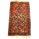 An early 20th century Afghan Belouch rug with octagonal guls, 73 by 43ins. (185 by 109cms.) (see