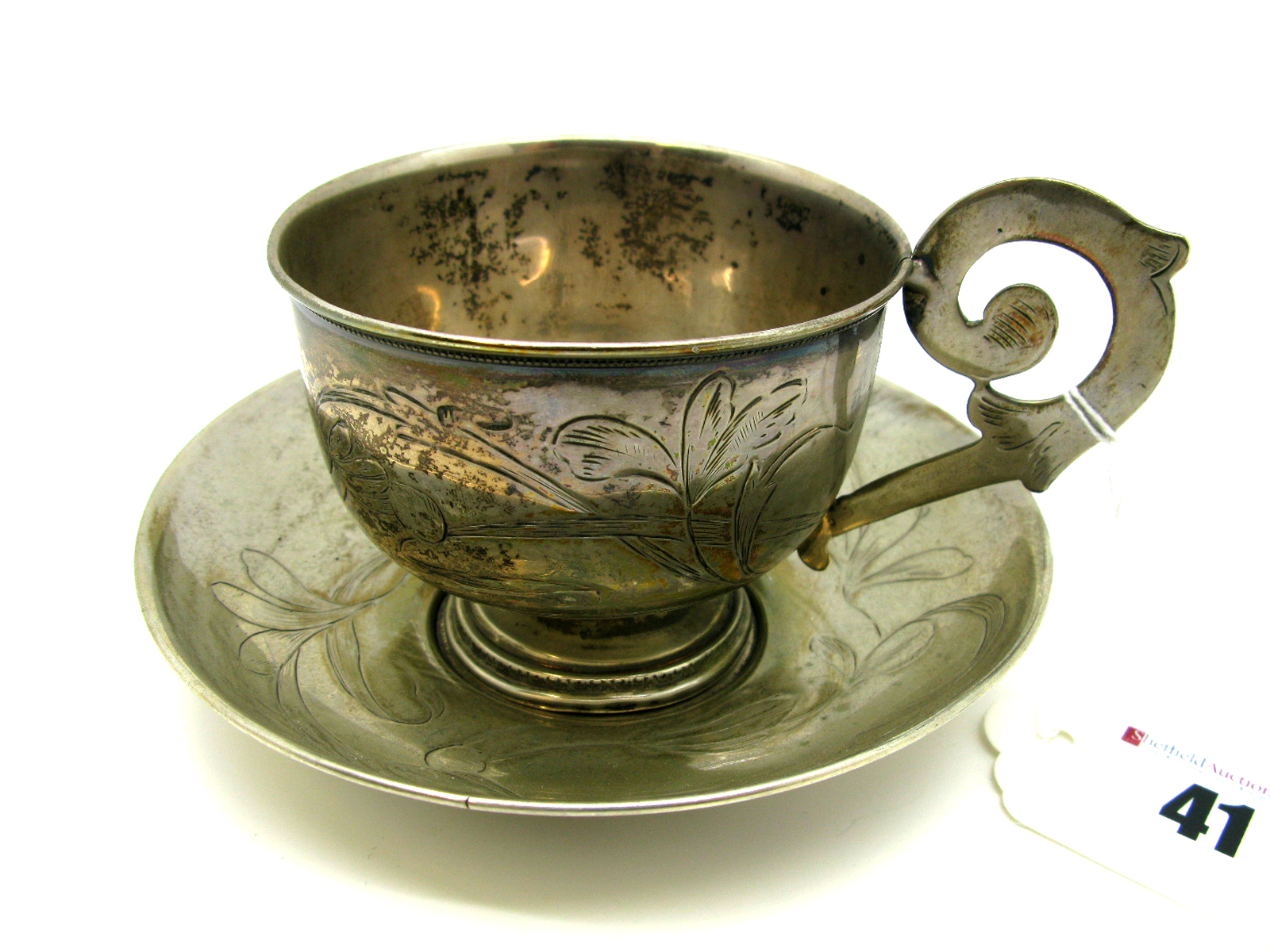 Lot 41 - A Russian Cup and Saucer, leaf engraved, the cup with flat scroll handle, the saucer 11.6cm