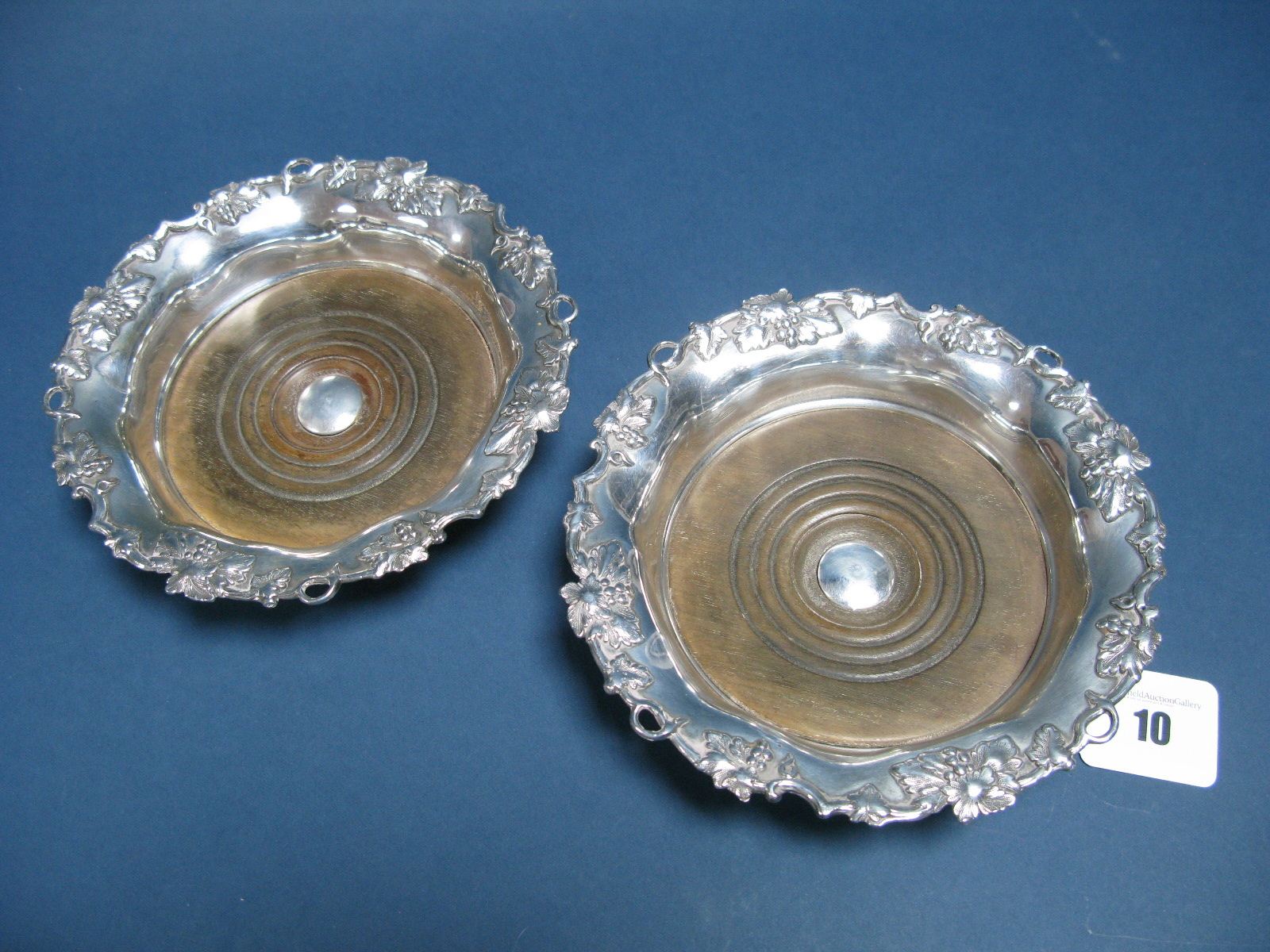 Lot 10 - A Pair of XIX Century Plated Bottle Coasters, each with shaped circular fruiting vine border and