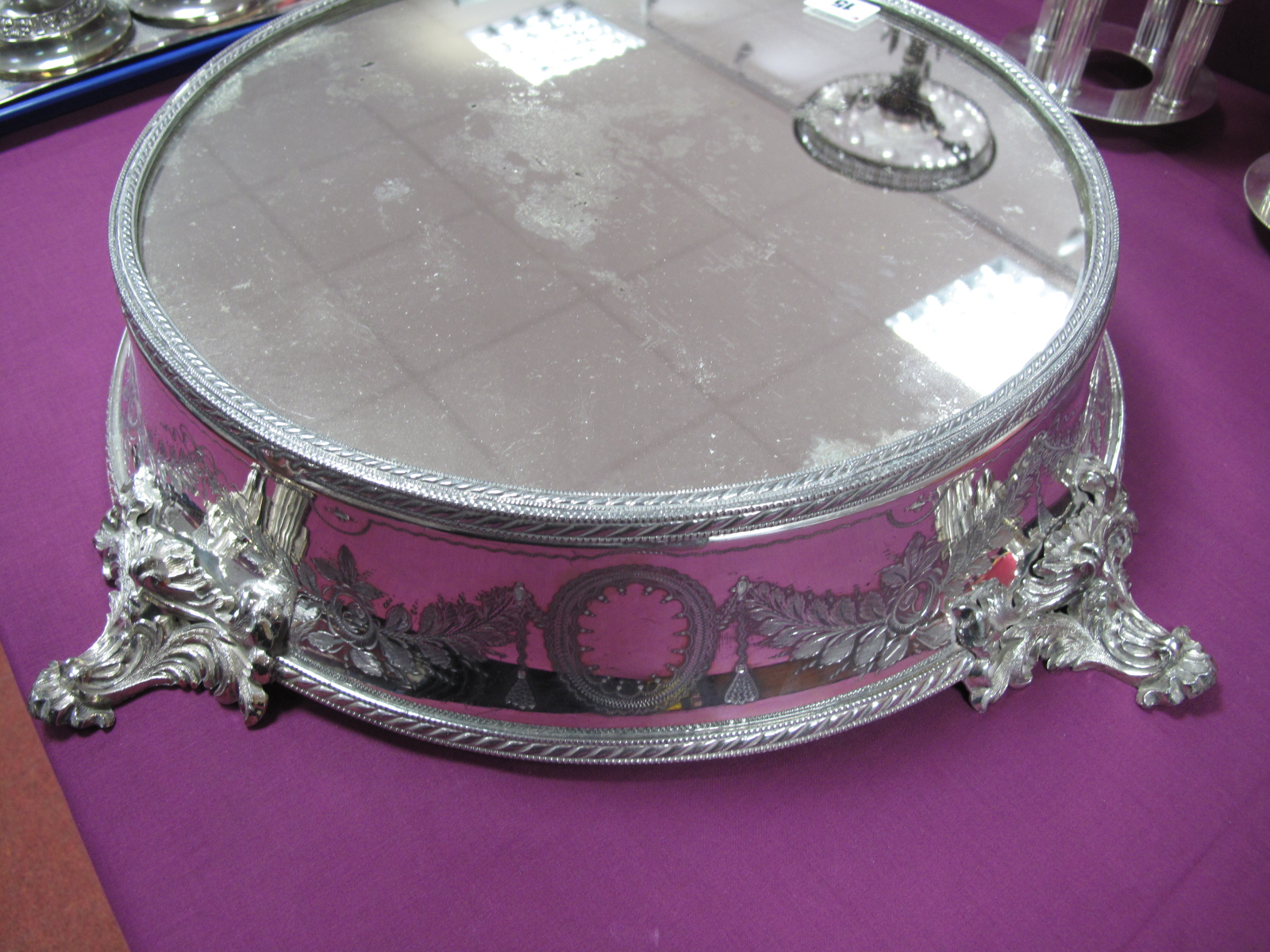 Lot 15 - A Late XIX / Early XX Century Plated Wedding Cake Stand, with mirrored plateau, within a ribbon tied
