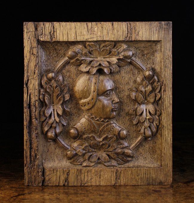 Lot 30 - A Small 16th Century Oak Panel carved with a profile of a woman's head in a ring adorned with