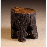 A Rustic Stool made from a section of tree trunk, approx 16 ins (41 cms) high, 14 ins (36 cms) wide.