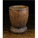 A Large Dug out Treen Mortar with naively carved fluting to the flared foot. 10 ins (25.