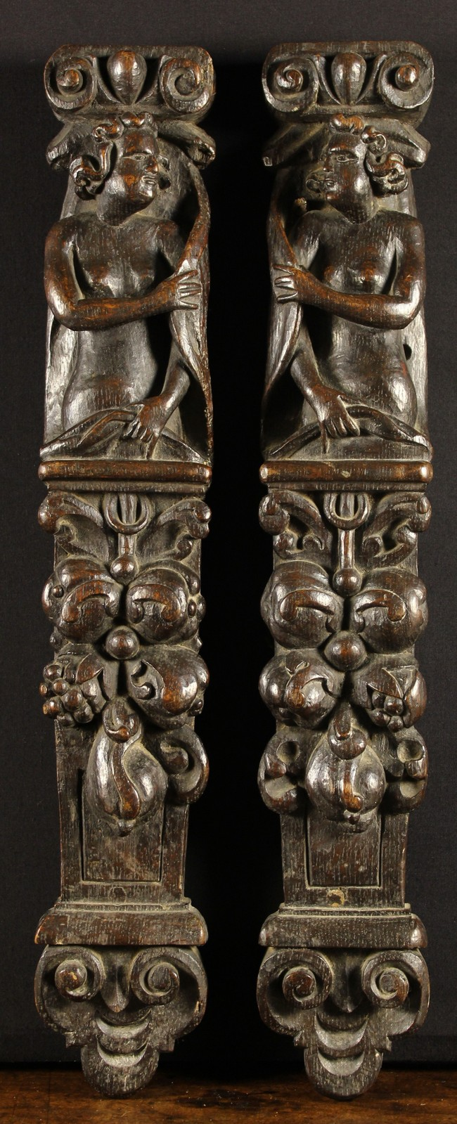 Lot 42 - A Pair of 17th Century Flemish Oak Caryatids carved with figures rising above pendant garlands of