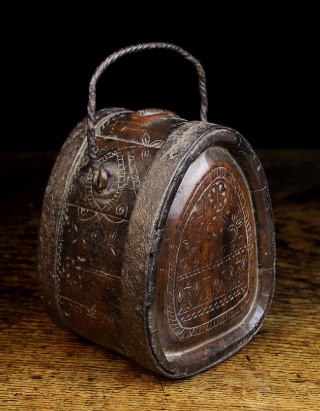 Lot 34 - An 18th Century Chip Carved Wooden flask bound in iron straps and fitted with a wrythen iron swing