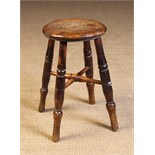 A 19th Century Kitchen Stool. The round top on turned legs united by a turned X-form stretcher.