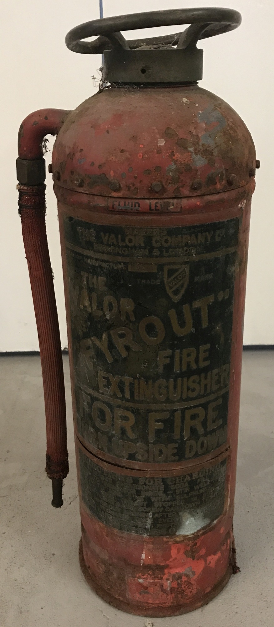 "A vintage red Valor ""Fyrout"" extinguisher, with original hose attachment."