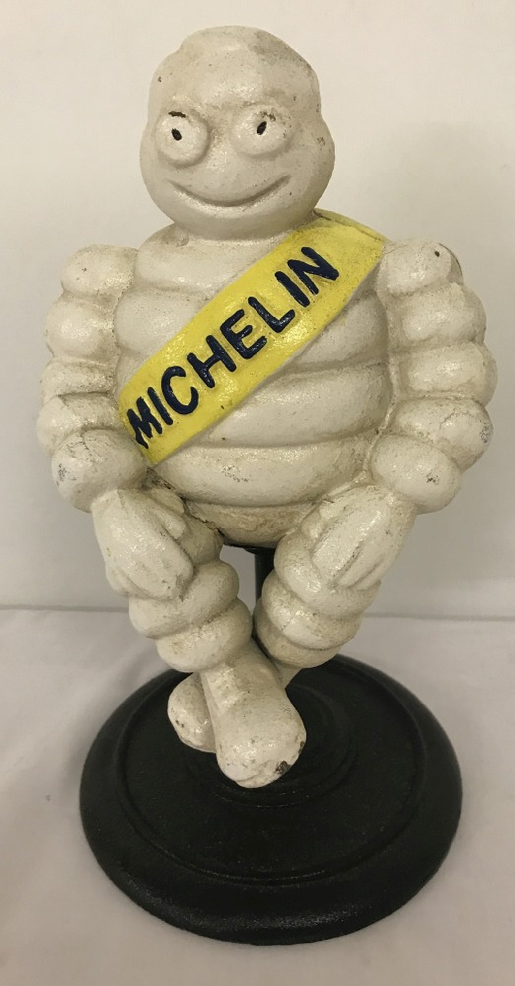 A cast iron sitting Michelin Man figurine on pedestal stand.