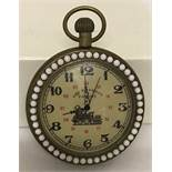 A brass cased pocket watch with beaded detail to surround front and back.
