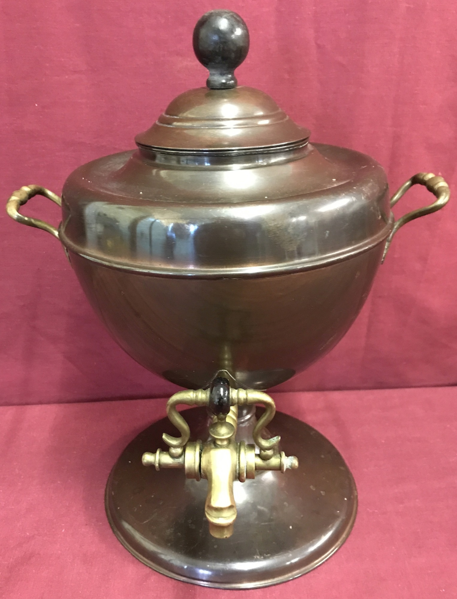 A vintage copper samovar with brass handles and tap and wooden finial.