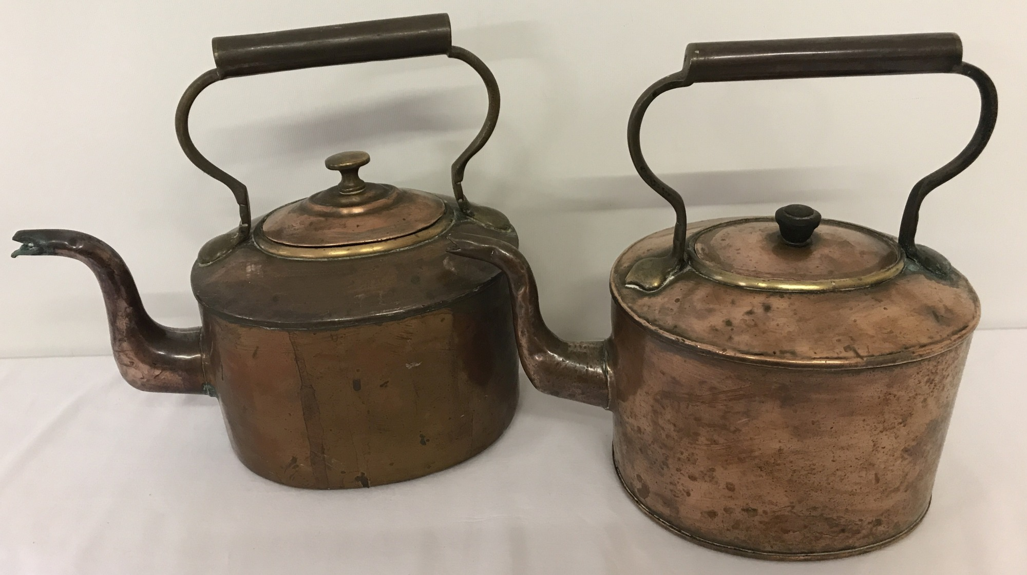 2 vintage oval shaped copper kettles with metal handles.