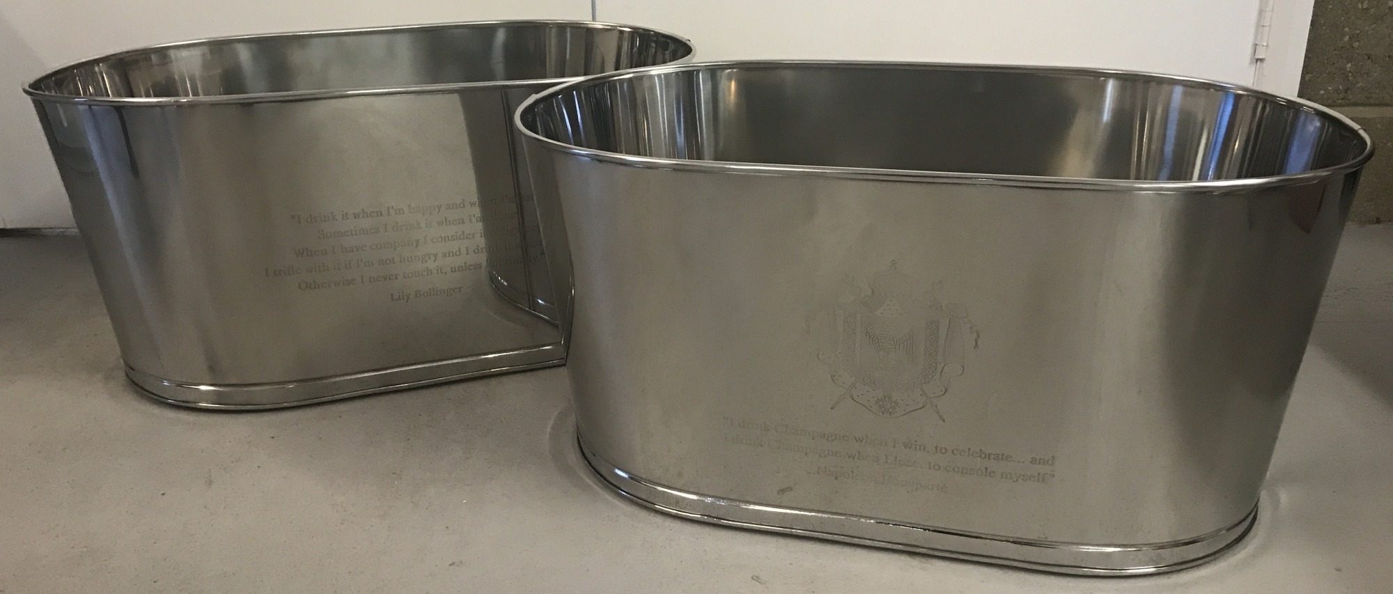 A pair of large Bollinger Champagne buckets with engraved details to sides.
