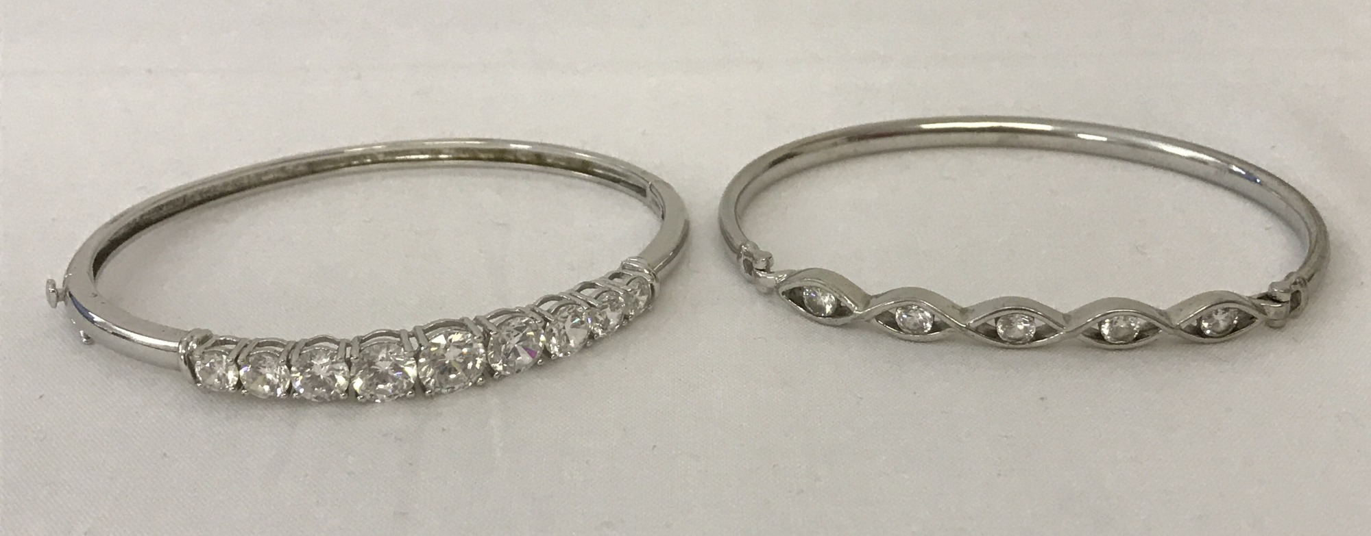 2 ladies silver bangles both set with cubic zirconia stones.