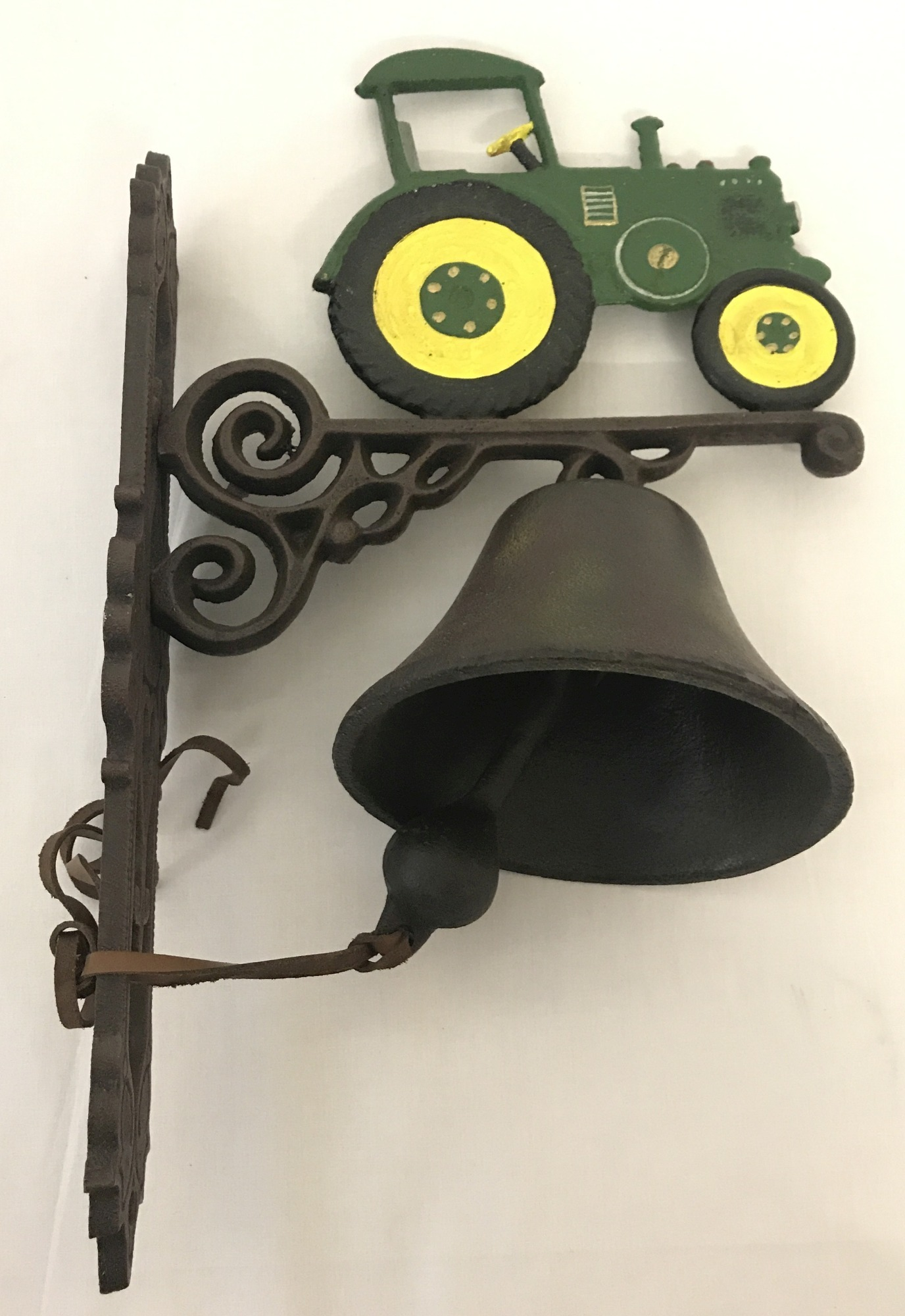 Lot 107 - A painted cast iron, wall hanging garden bell with tractor detail.