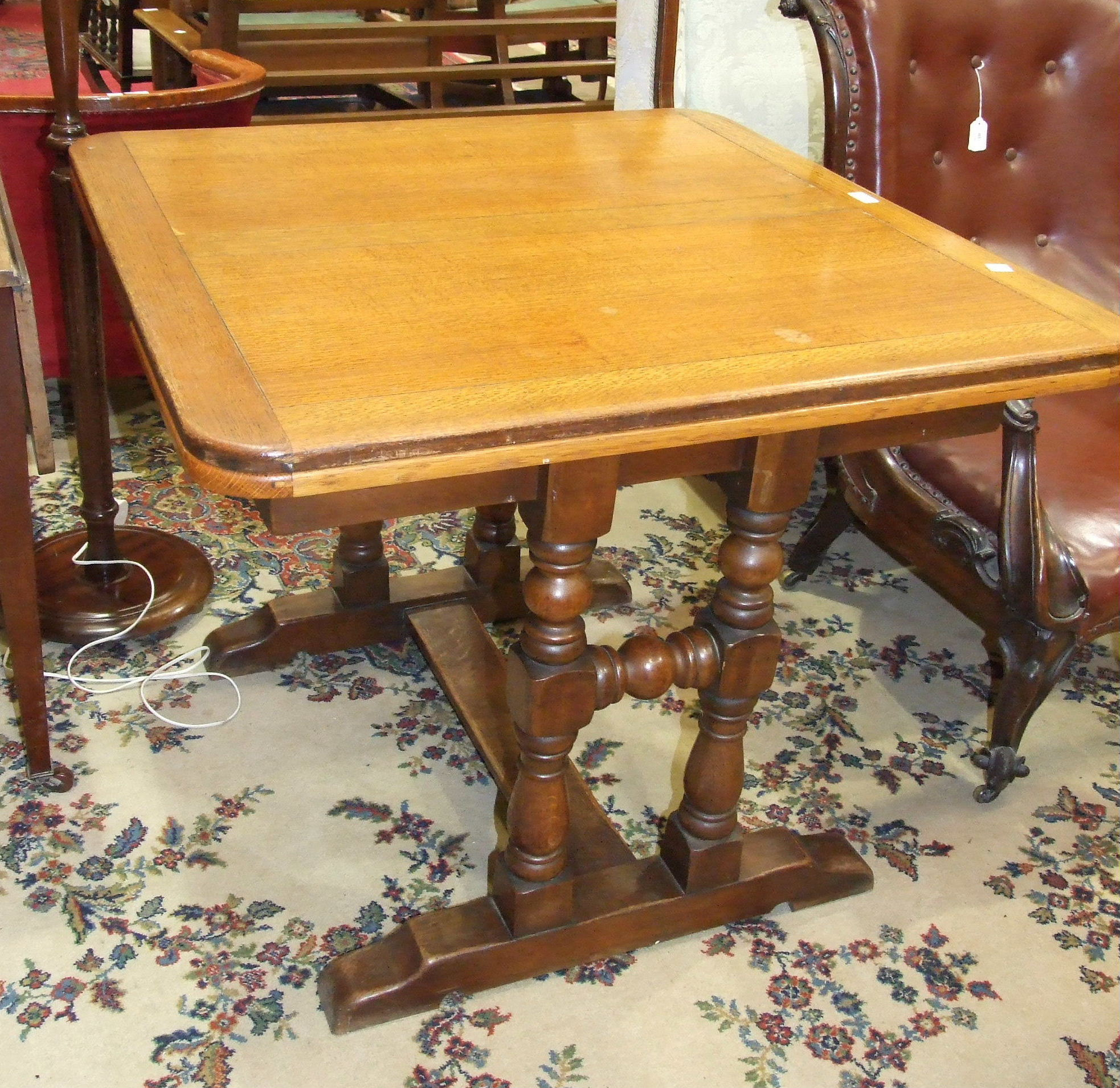 Lot 3 - An oak draw leaf dining table on turned end-supports united by a stretcher, 150 x 1=90cm open, and