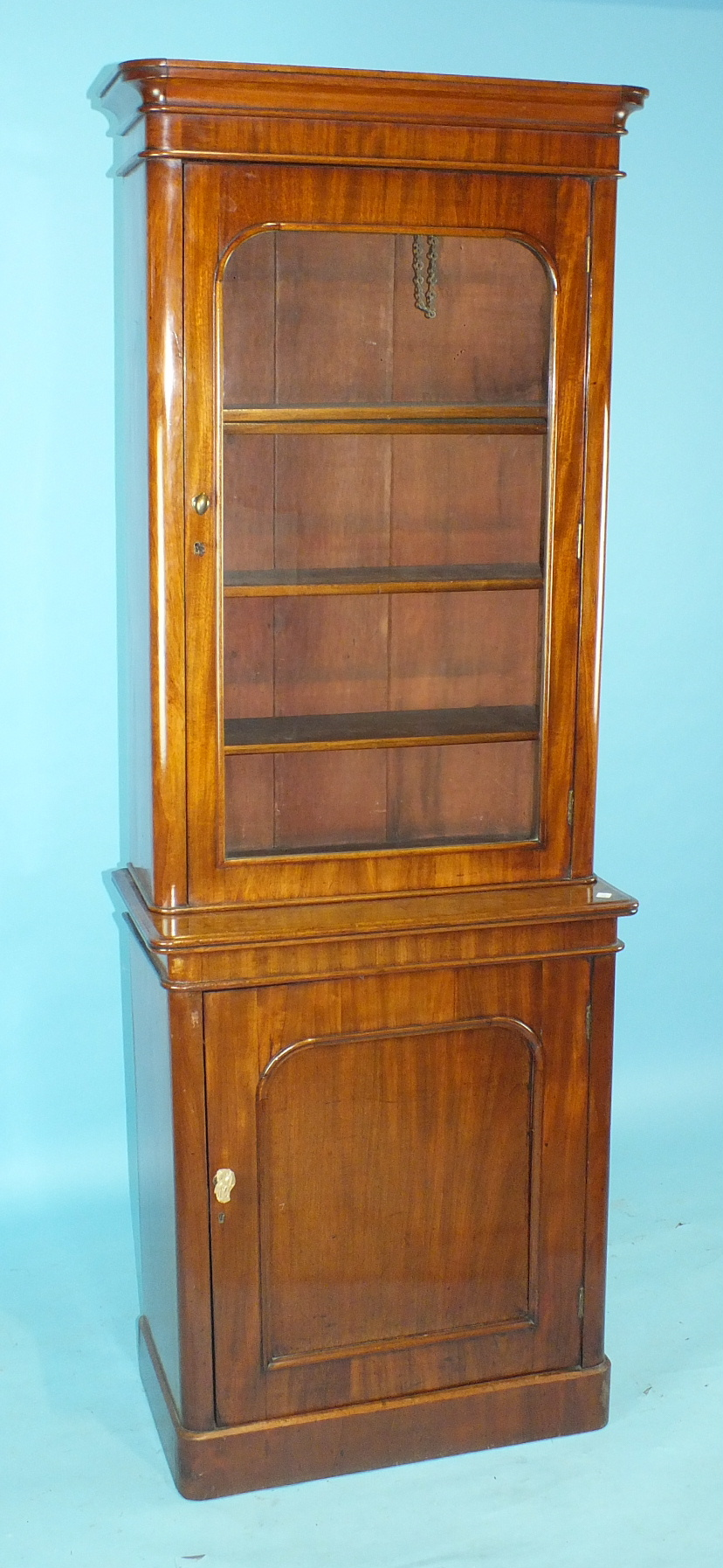 A Victorian mahogany narrow bookcase with single glazed door above a panelled door, 80cm wide, 213cm