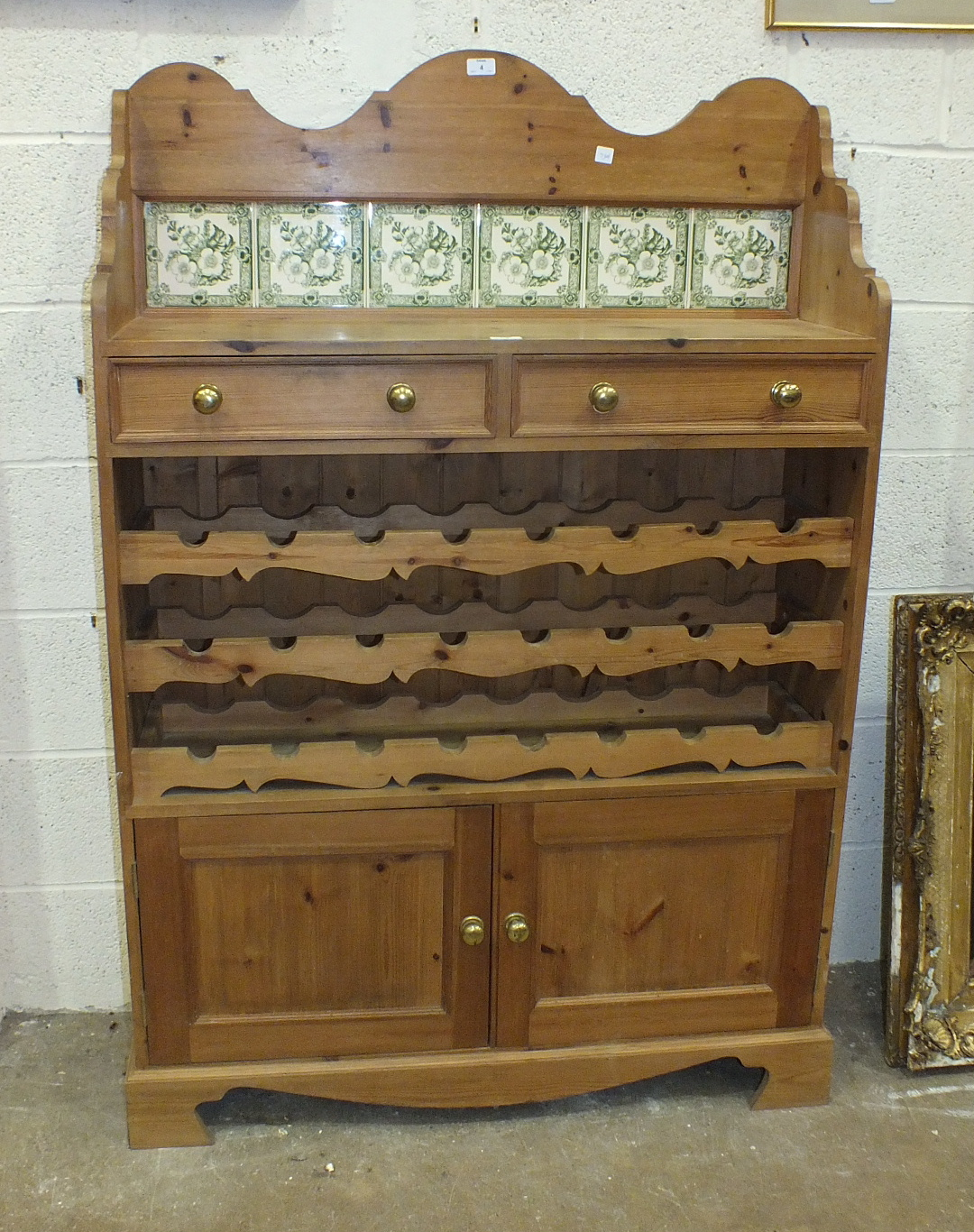 A pine low dresser, the tiled back and shelf above two drawers, three bottle racks and a pair of