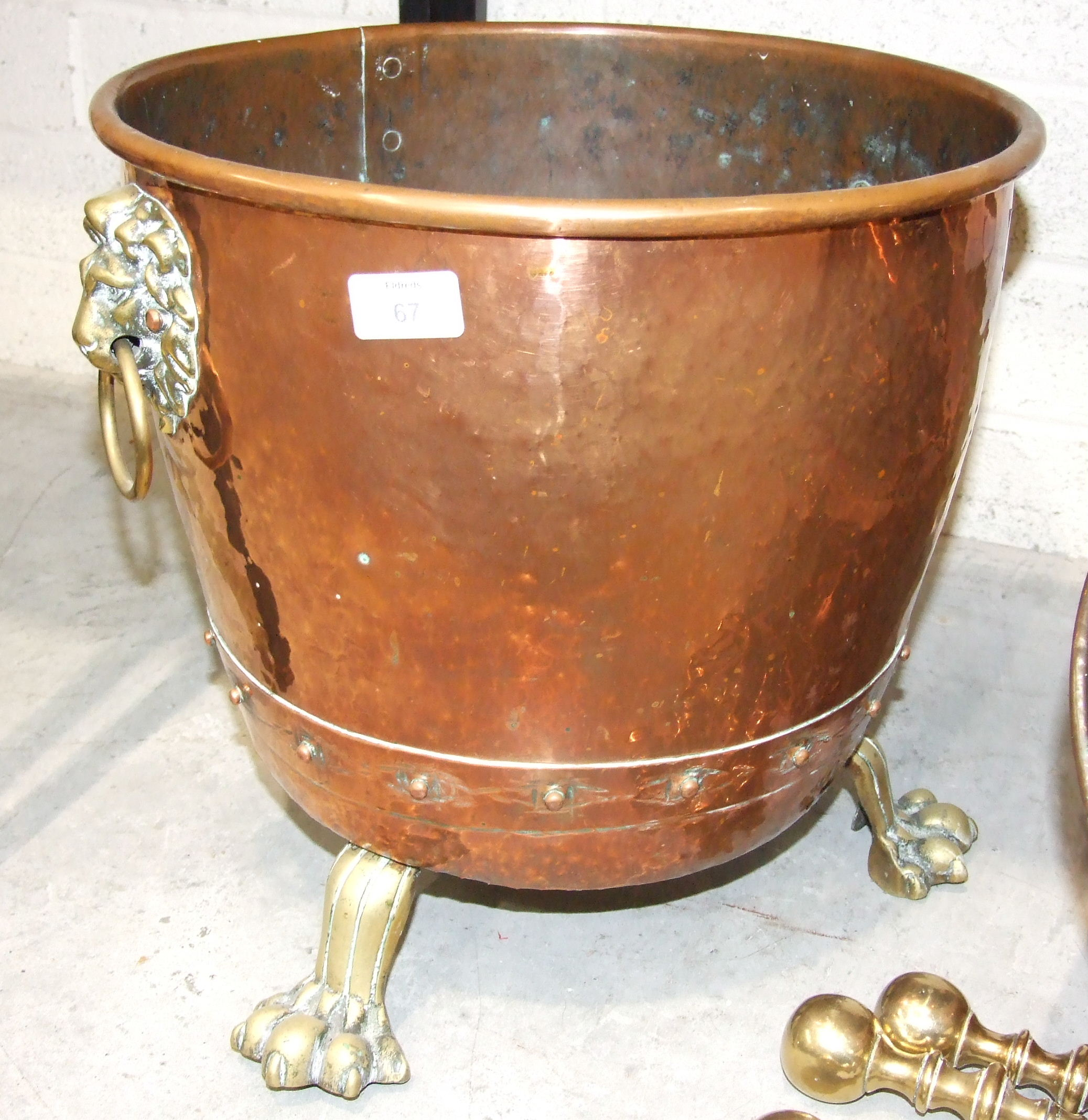 Lot 67 - A copper coal bucket with lion's head handles and claw feet, 38cm diameter, 38cm high, a copper coal