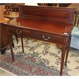 An Edwardian mahogany hall table, the low back above a rectangular top and two frieze drawers, on