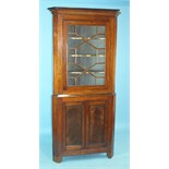 A Georgian mahogany corner cupboard, the moulded cornice above an astragal-glazed door and a pair of