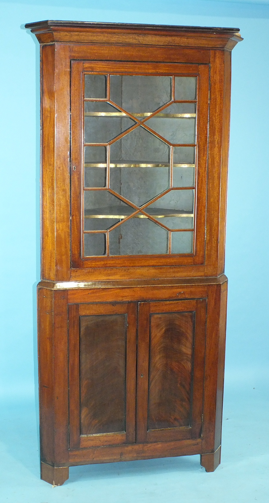 Lot 37 - A Georgian mahogany corner cupboard, the moulded cornice above an astragal-glazed door and a pair of