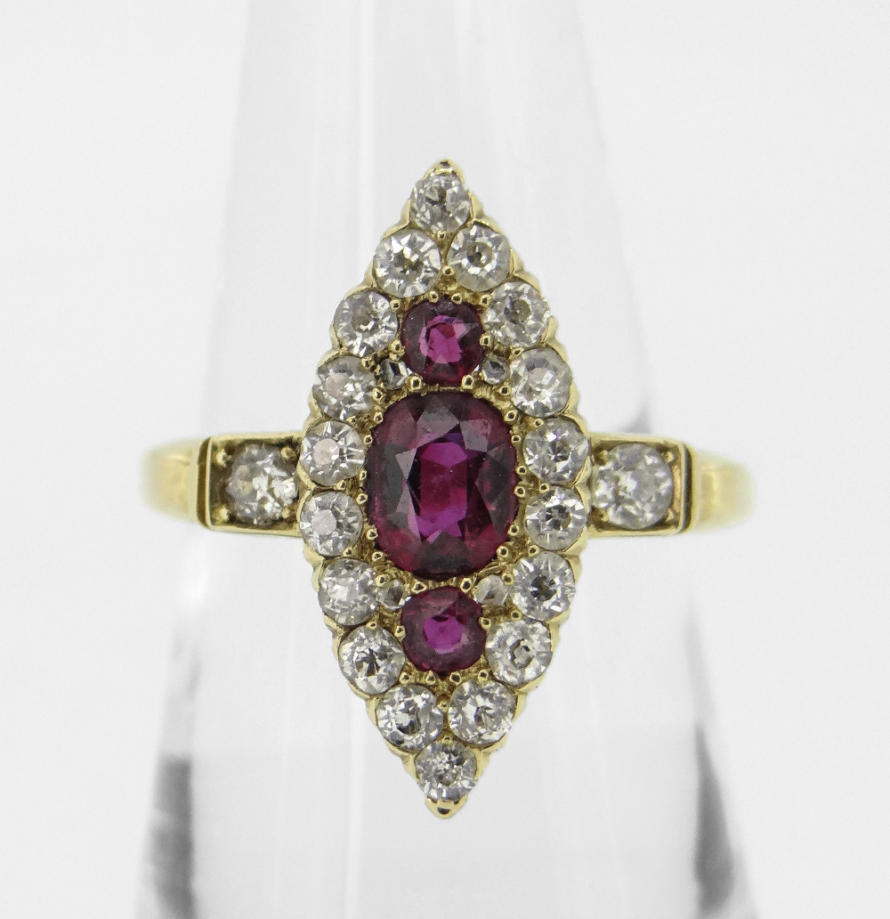 18CT YELLOW GOLD MARQUISE RUBY & DIAMOND CLUSTER RING, the central ruby (5.5 x 4.5mms) flanked by