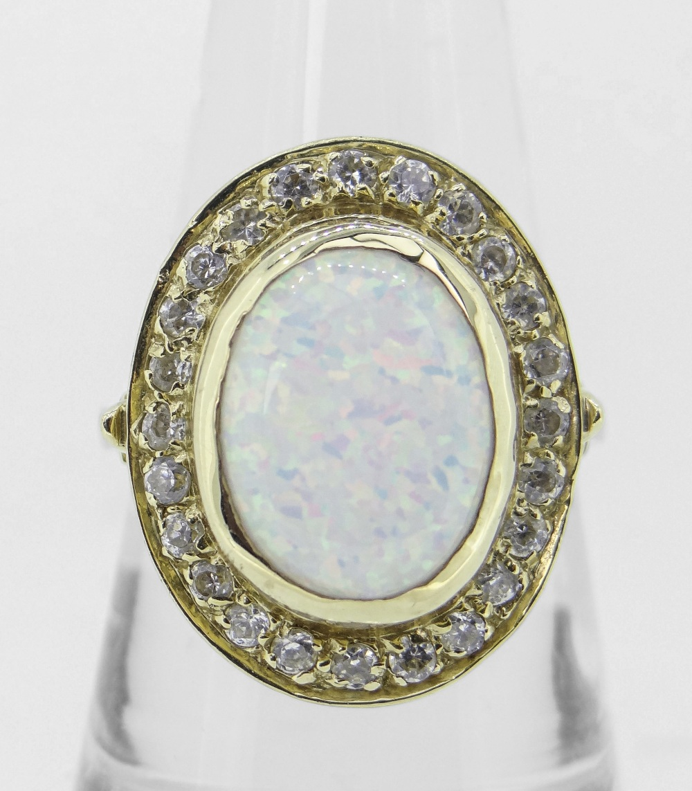14K (585) YELLOW GOLD OVAL OPAL DRESS RING having border of twenty-four small diamonds, 6.8 grams.