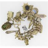 9CT YELLOW GOLD CHARM BRACELET having approximately 30 yellow metal charms of varying design to