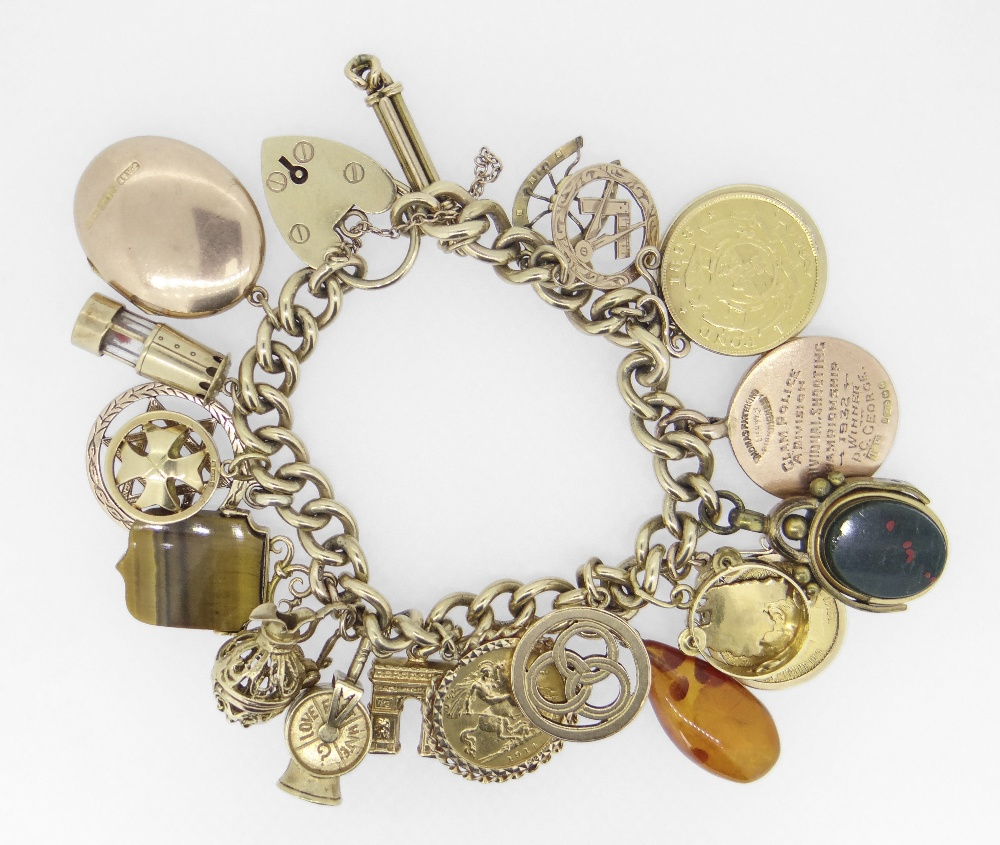 9CT YELLOW GOLD CURB LINK CHARM BRACELET HAVING HEART SHAPED PADLOCK and assorted coins and charms