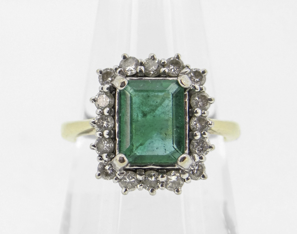18CT YELLOW GOLD EMERALD & DIAMOND DRESS RING, the central emerald (7 x 9mms) surrounded by