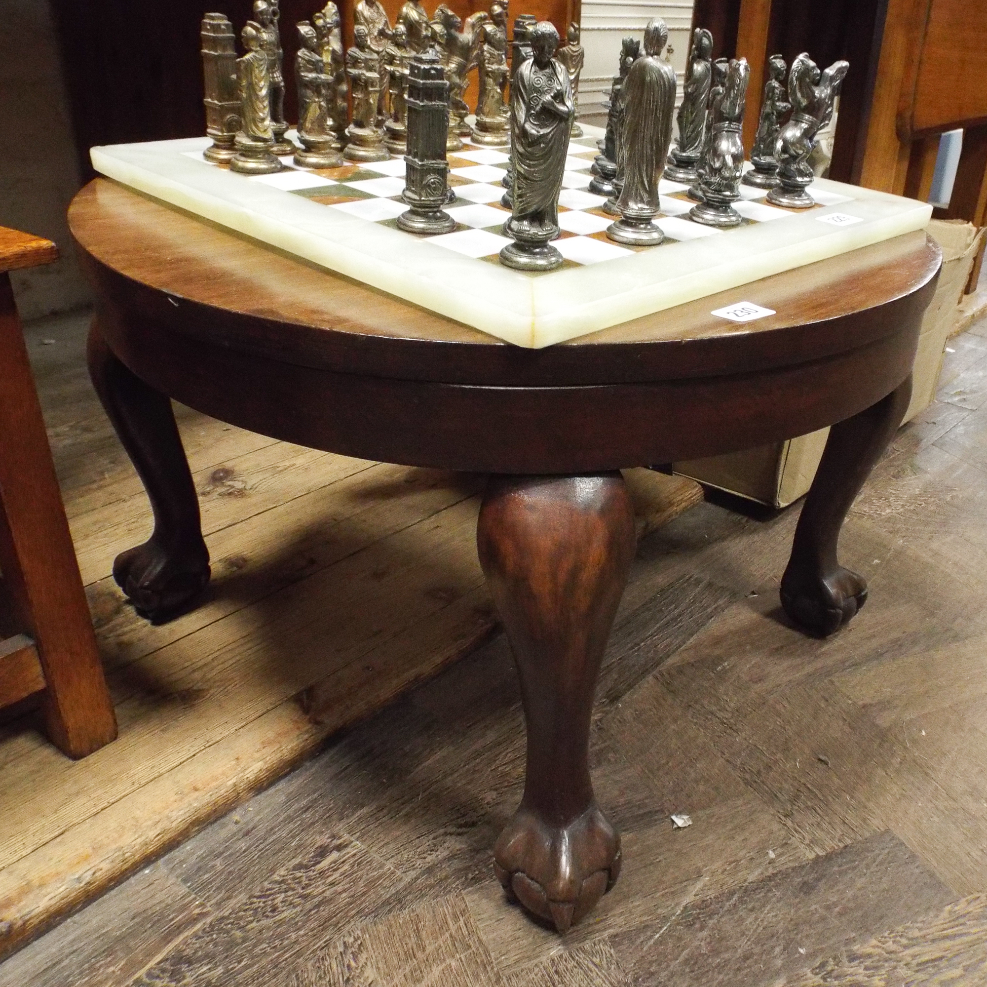 A Circular Mahogany Coffee Table Standing On Claw And Ball