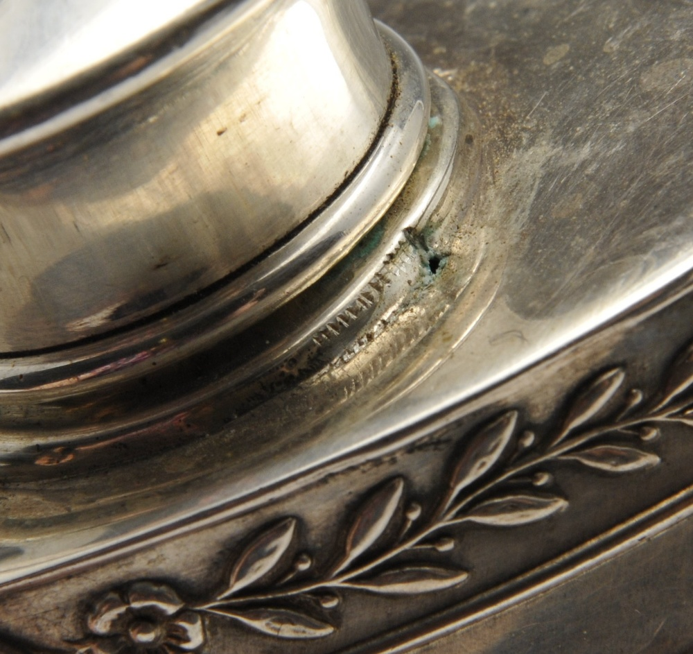 Lot 127 - An early twentieth century silver tea caddy of oval form, decorated with a trailing leaf border