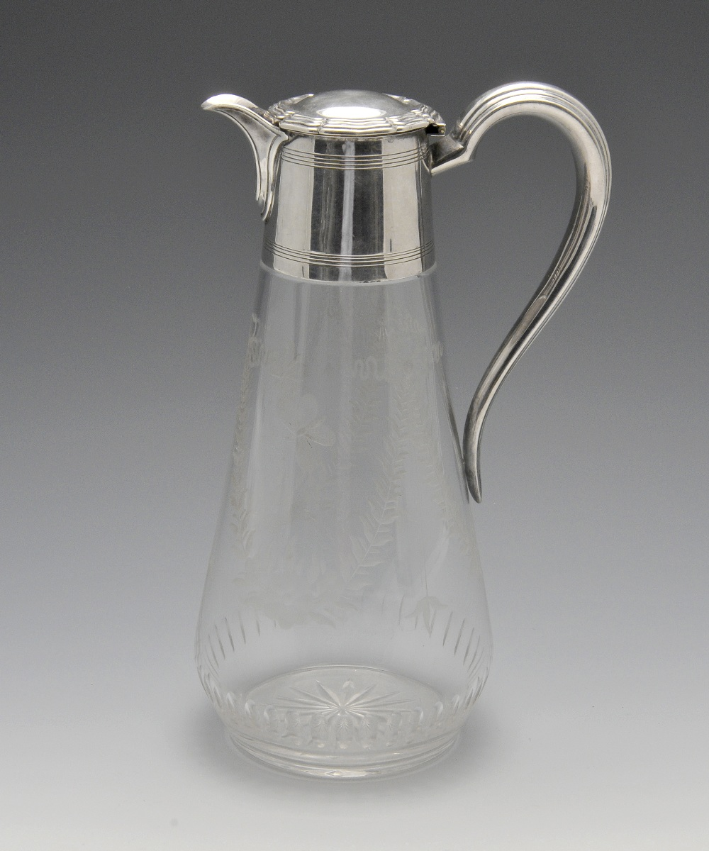 Lot 117 - An early twentieth century silver mounted claret jug, the tapering glass body etched with floral