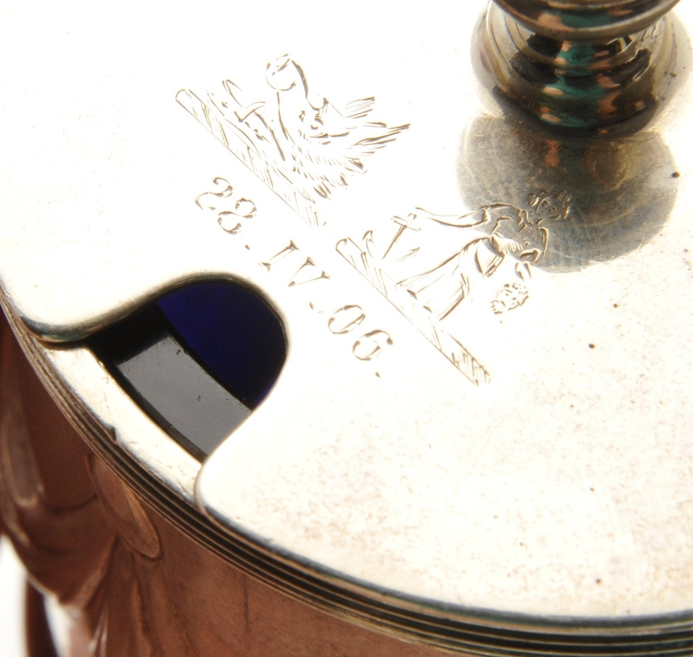 Lot 151 - An Edwardian silver mustard pot, the drum form embossed with swags within reeded borders, hinged