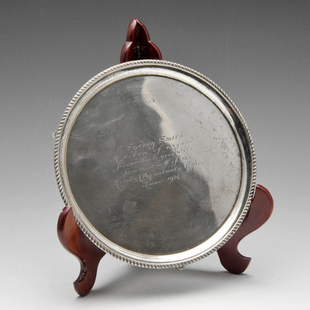 Lot 226 - A 1920's small silver salver of circular form with oblique gadrooning to rim and raised on three