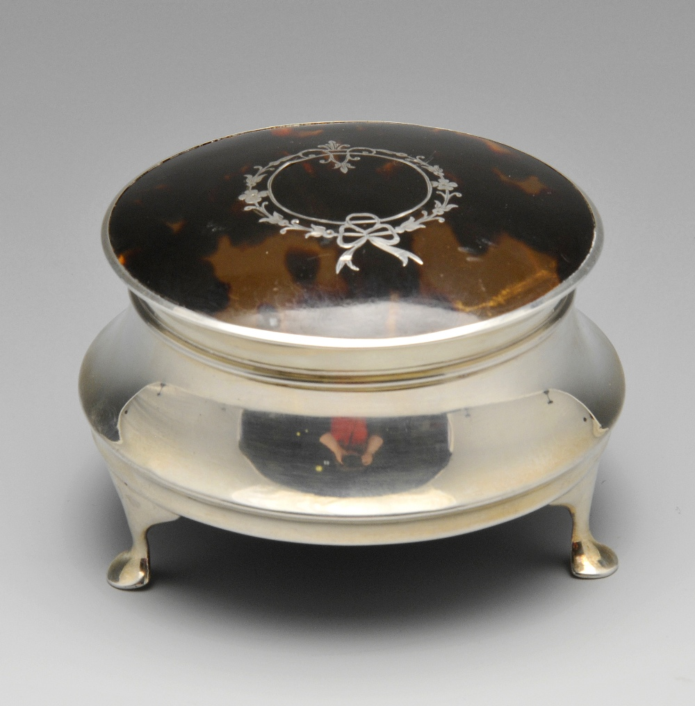 Lot 721 - A 1920's silver tortoiseshell jewellery or trinket box, the circular capstan body with hinged