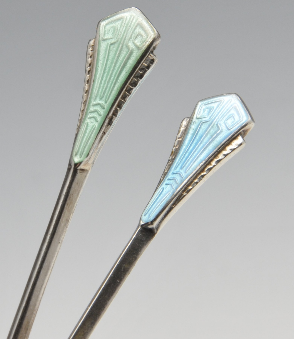 Lot 518 - A cased set of Art Deco enamelled coffee spoons, the faceted bowls with shaped shoulders rising to