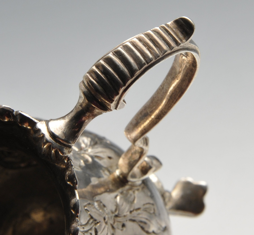 Lot 134 - A George III silver cream jug, the bellied form with oblique fluting and beading amidst floral