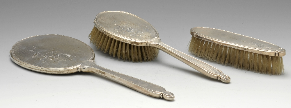 Lot 369 - A 1950's silver three piece dressing table set comprising hand mirror, hairbrush and clothes