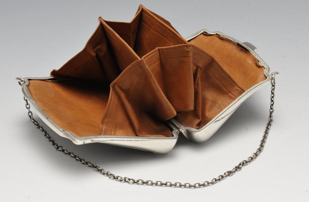 Lot 654 - An early twentieth century silver mounted tortoiseshell purse, the hinged and tapered body inlaid