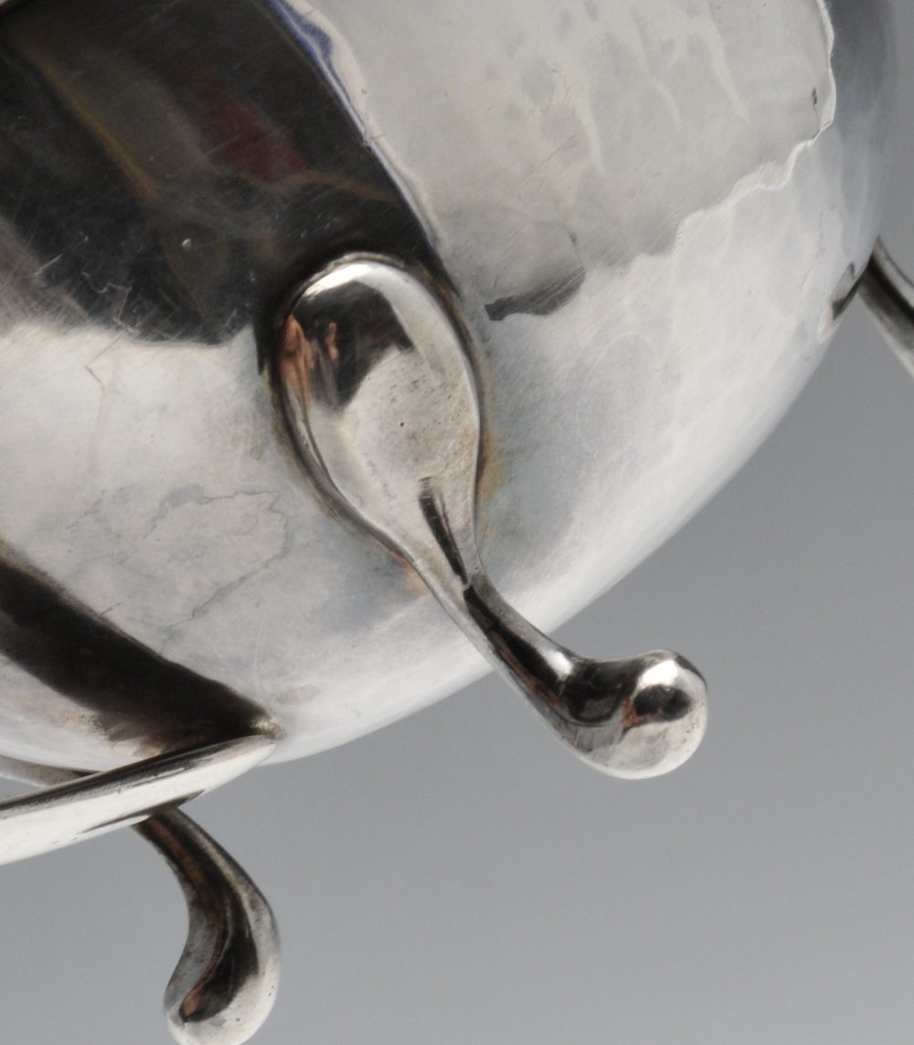 Lot 467 - An Italian silver sauce boat of planished form with moulded rim, split loop handle and raised on
