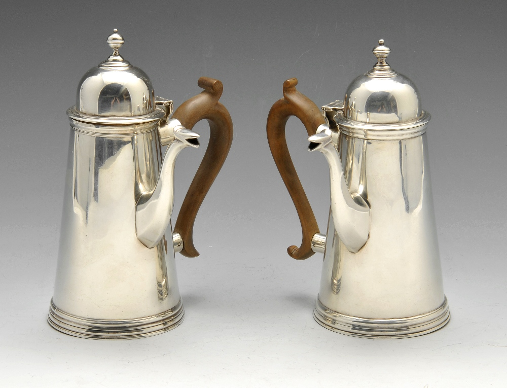 Lot 175 - A pair of Edwardian silver chocolate pots of plain tapering form with domed hinged covers and