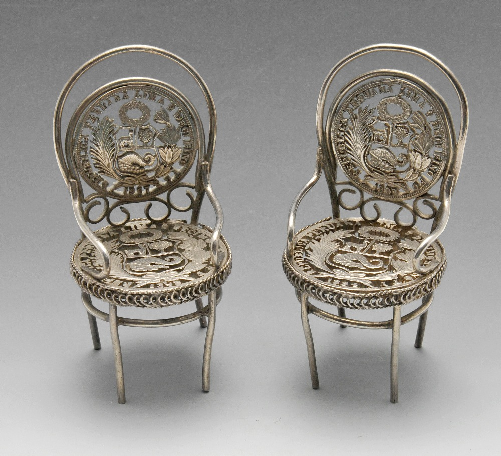 Lot 629 - A pair of toy or miniature pierced coin set chairs. Height measuring 7.5 cm, gross weight 85