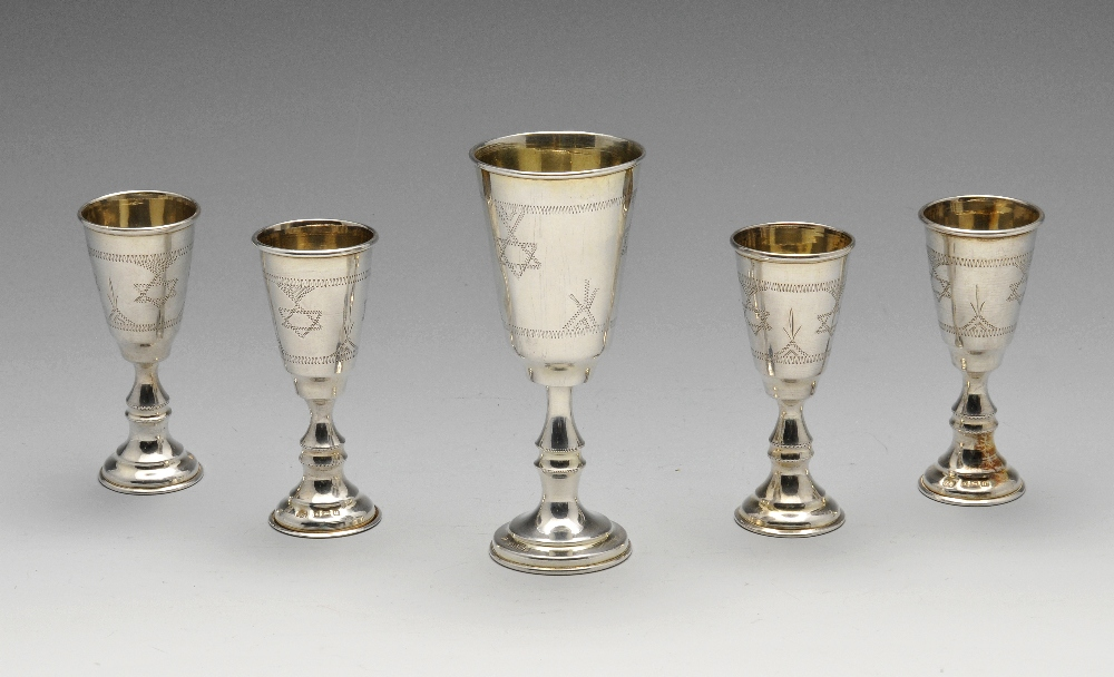 Lot 229 - A set of four George V silver Kiddush cups, engraved with Star of David border to the tall